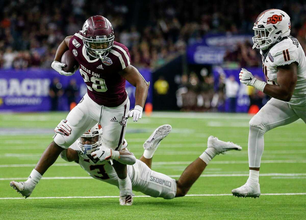 Texas A&M running back Isaiah Spiller, trying to escape Oklahoma State's Tre Sterling at the Texas Bowl, stepped in as the Aggies' starter as a freshman in 2019.