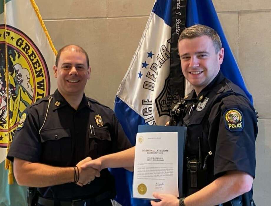 Greenwich Police Officer Kevin Ingraham, right, is recognized by Capt. Mark Zuccerella for a medical intervention involving a drug overdose. Photo: / Greenwich Police Department