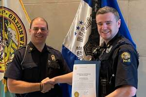 Greenwich Police Officer Kevin Ingraham, right, is recognized by Capt. Mark Zuccerella for a medical intervention involving a drug overdose.
