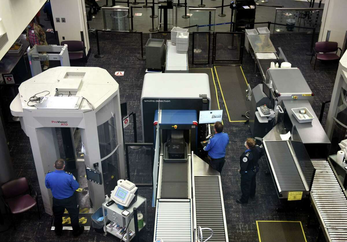 TSA officers demonstrate the new 3-D imaging scanner, center, at the passenger security screening area in Albany International Airport on Monday, Sept. 21, 2020, in Colonie, N.Y. The new security device creates a 3-D image that can be viewed and rotated on three axes. It gives officers improved viewing of carry-on luggage that they say will help reduce the need to open bags and re-scan items. (Will Waldron/Times Union)