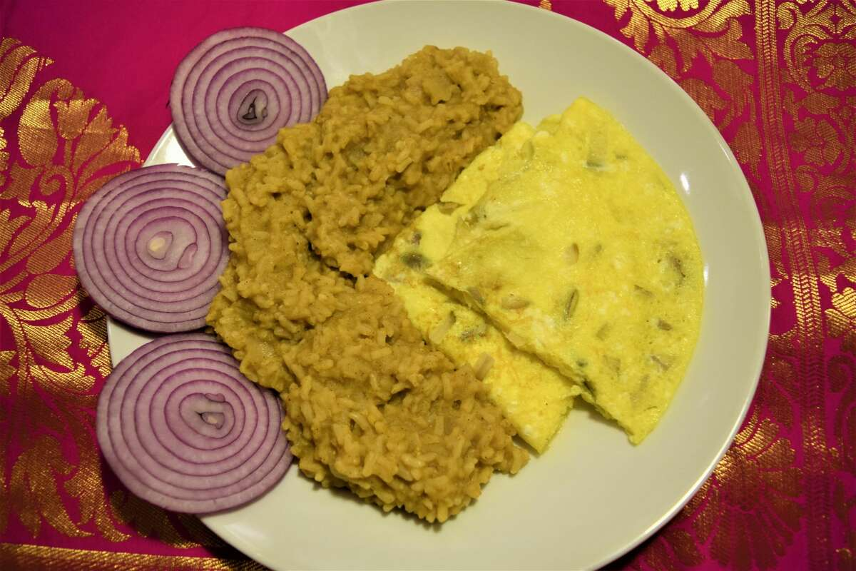 Ammu's rainy day khichuri with a side of fried eggs and red onions.