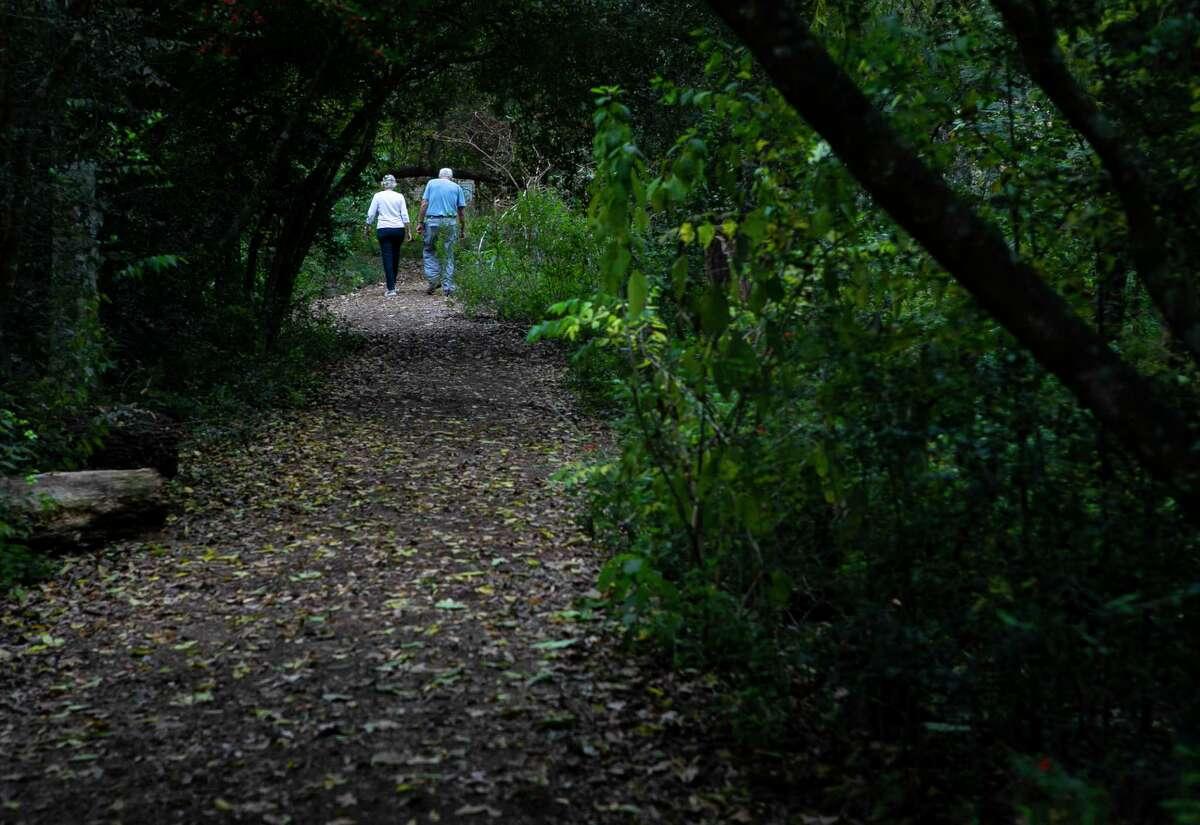People walk along the trails at the Houston Arboretum, Monday, Nov. 25, 2019.