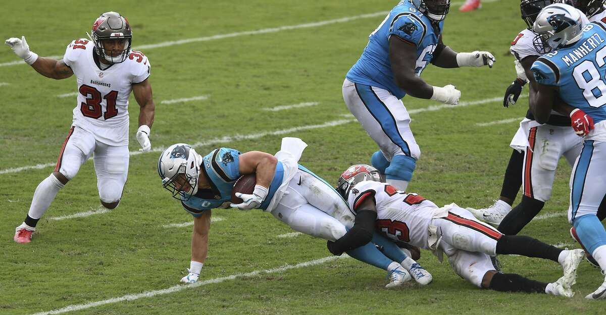 Carolina Panthers running back Christian McCaffrey (22) gets tripped up by Tampa Bay Buccaneers free safety Jordan Whitehead (33) during the second half of an NFL football game Sunday, Sept. 20, 2020, in Tampa, Fla. (AP Photo/Jason Behnken)