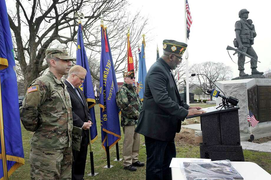 Tom Saadi, of Danbury, left, state Veterans Affairs Commissioner, and Mayor Mark Boughton listen as Ronald Agard with VFW Post 149 reads the names of Danbury area soldiers that are missing in action or prisoners of war. Vietnam veterans are remembered Thursday, March 29, 2018, with a ceremony at the Vietnam War Memorial at Rogers Park in Danbury. March 29 is National Vietnam War Veterans Day. On that day in 1973 combat and combat support units withdrew from Vietnam. Photo: Carol Kaliff / Hearst Connecticut Media / The News-Times
