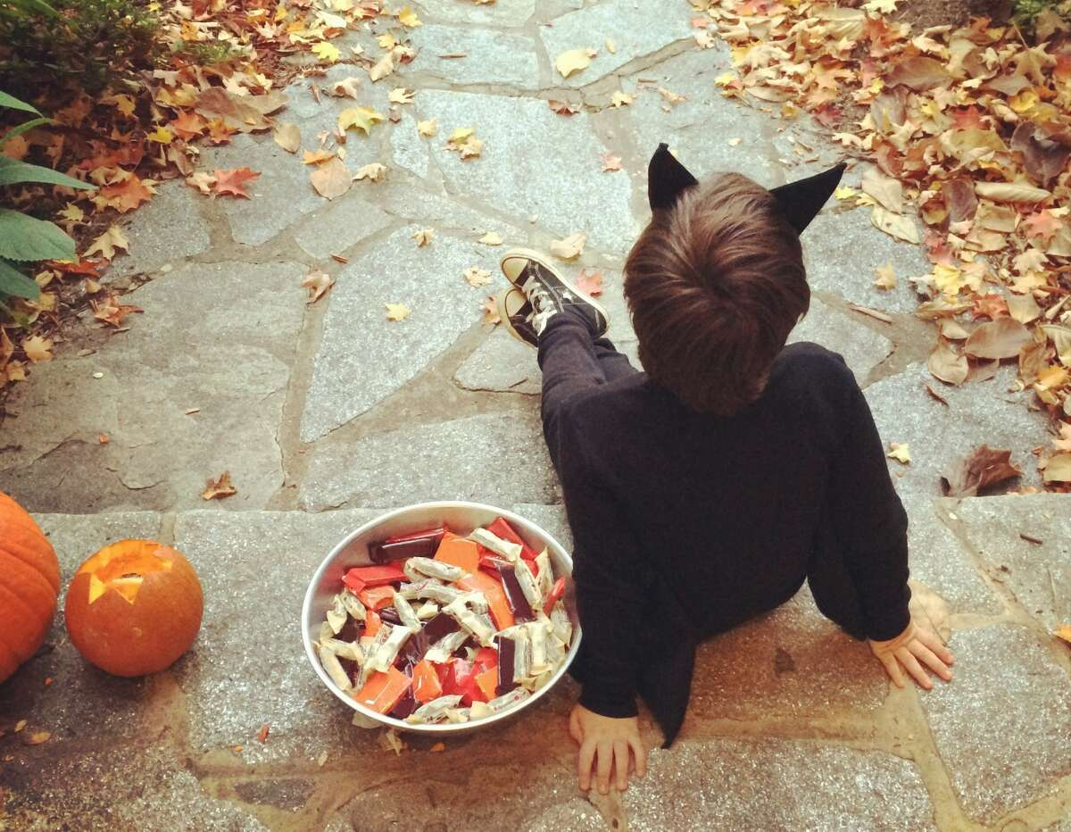 View of the back of a little boy sitting down on his front porch dressed up in a bat costume and handing out Halloween candy. M&M's Ranking: Third place Pounds sold: 1,582 M&M's landed in third place as Connecticut's favorite candy. These mini pieces of chocolate goodness are easy to pop into your mouth and even easier to lose count of.