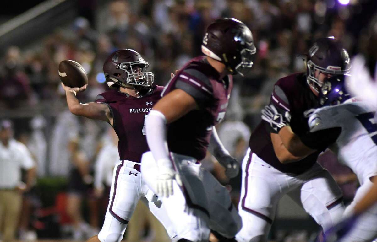 Magnolia junior quarterback Travis Moore, left, sets to launch a deept throw to Bulldogs senior wide receiver Ben Renfro against the Montgomery defense in the second quarter of their matchup at Magnolia Stadium on Friday, Sept. 13, 2019.