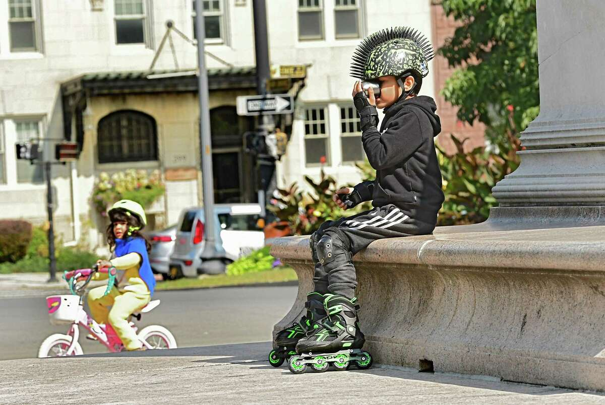 Cyrus D'Cruz, 8, of Albany takes a break from rollerblading around the Soldiers and Sailors?• Monument to get a drink in Washington Park on Monday, Sept. 21, 2020 in Albany, N.Y. His sister Sara Simone D'Cruz, 4, is seen riding her bike. (Lori Van Buren/Times Union)