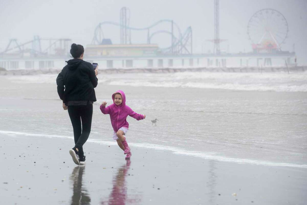 Brittany Griffin walks on the beach with her daughter, June, 3, as they watch the rough surf churned up by Tropical Storm Beta Monday in Galveston. As Beta continues to meander off the Texas coast, local officials are prepared for potential flooding but as of Monday the rainfall forecast had dropped below five inches for Montgomery County.