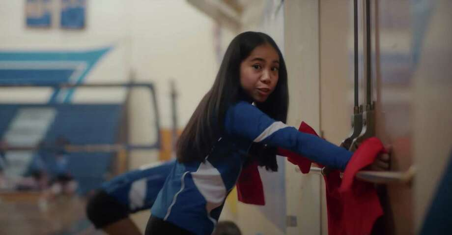 'This jacket is a real must-have,' a student says in Sandy Hook Promise's 'Back-to-School Essentials' public service announcement as she hurries to tie her jacket on the door handles of a school gym during an active school shooting. Photo: YouTube / Sandy Hook Promise