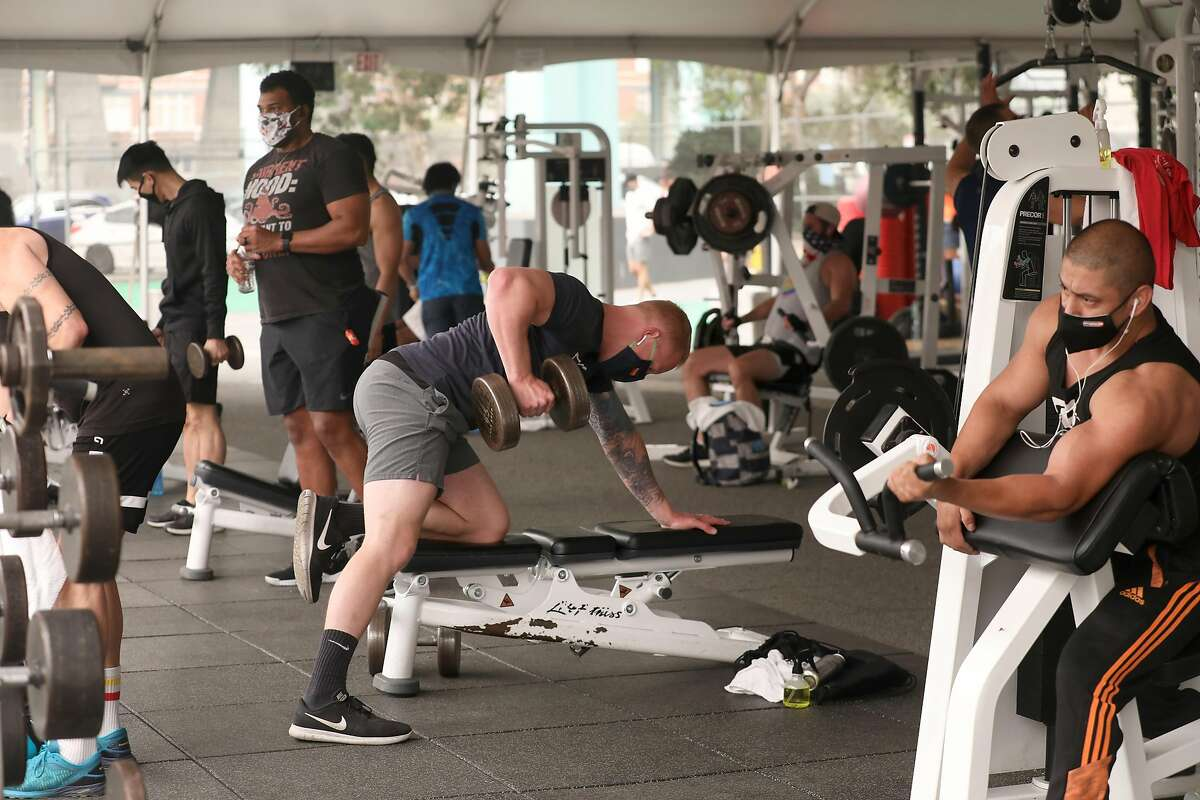 Edward Britten (left), 4 year member, and Craig Cuffney (middle), 5 year member, and maintenance team member Gerardo Pineda (right) workout for the second day at the outdoor tent of SF Fitness on Brannan at 9th streets on Thursday, Sept. 10, 2020, in San Francisco, Calif.