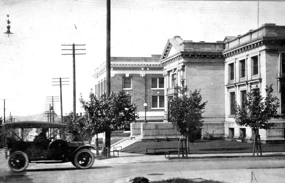 A vehicle zooms past the Manistee Public Library on First Street circa 1920. (Manistee County Historical Museum photo)