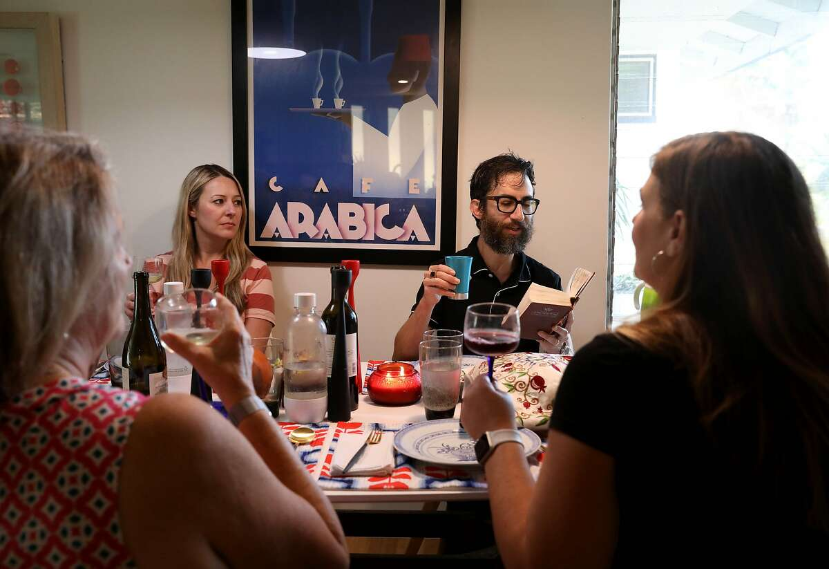 (Left to right) Gabi Moskowitz's mother Louise Packard, her sister-in-law Jennifer Moskowitz, husband Evan Wolkenstein, and Gabi listen to Evan as he reads from the Torah as they raise glasses of wine at dinner for Rosh Hashanah on Friday, September 18, 2020, in Novato, Calif. Gabi is celebrating with her family for a small dinner at home.