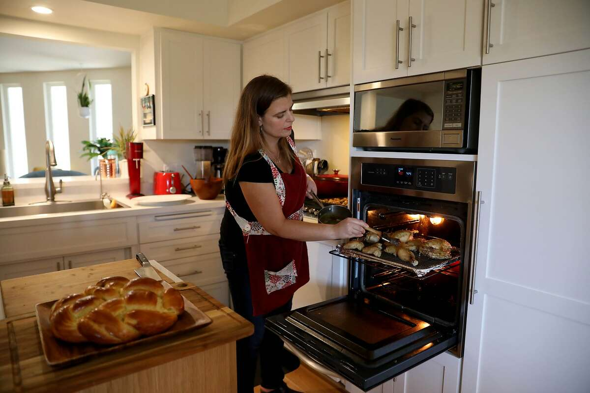 Gabi Moskowitz bakes honey jalapeño chicken in her kitchen for Rosh Hashanah on Friday, September 18, 2020, in Novato, Calif. She is celebrating with her family for a small dinner at home.