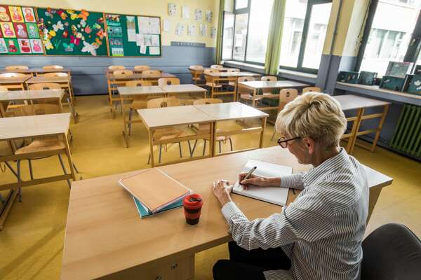 Mature female teacher writing notes in her notebook in empty classroom.
