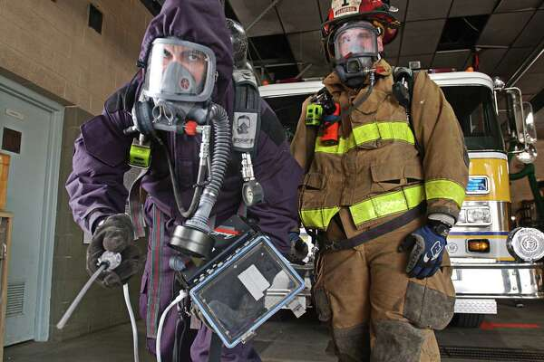 In this file photo from 2003, then Branford Firefighter/ Paramedics Shaun Heffernan, left, and James Murray Jr. show off traditional firefighting gear, right and new chemical biohazard gear that they were currently training on.