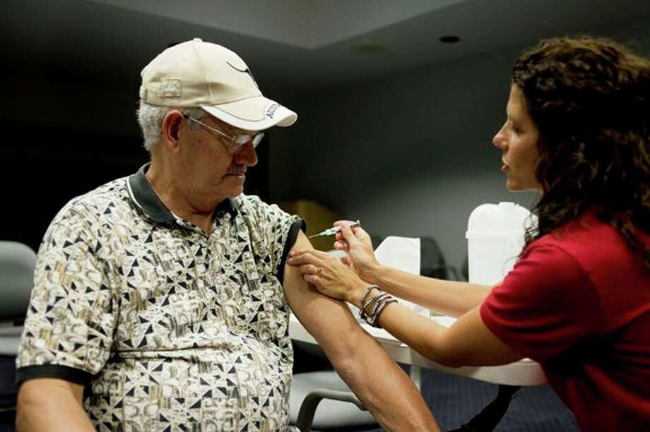 NEIL BLAKE | nblake@mdn.net Jim Chambers of Sanford gets a flu shot from Travel Immunization Nurse Nicole Swanton at the Midland County Services Building on Wednesday. The clinic was the first clinic this fall, but immunizations are available by appointment during the week. / Midland Daily News