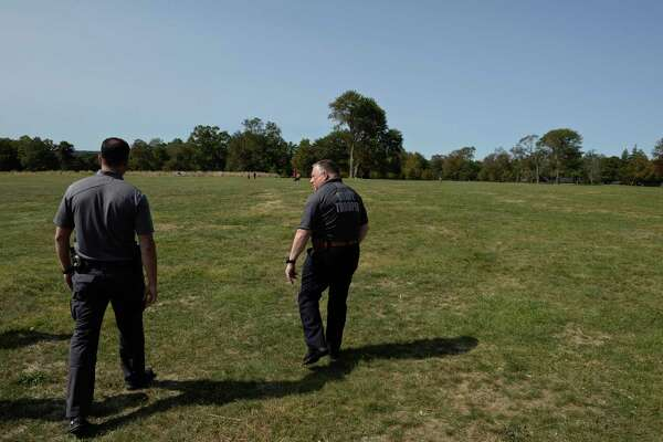 Detective John Kimball, right, and Officer Thomas Patten, left, New Canaan Police Department, who is assigned to the investigation division, walk through Waveny Park in New Canaan.