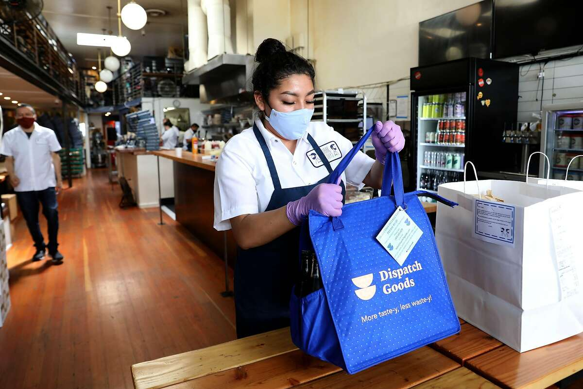 Joana Rico places a Dispatch Goods bag on a table in the front of Square Pie Guys on Friday, September 18, 2020, in San Francisco, Calif. People are ordering more takeout than ever before, which also means they're throwing out a lot of single-use containers. It's been a blow to the Bay Area's zero waste movement, which was growing earlier this year thanks to several new city ordinances and has since seemingly screeched to a halt. But the pandemic hasn't stopped Lindsey Hoell, the founder of San Francisco startup Dispatch Goods, from trying to bring a radical, zero-waste solution to the takeout world. Her vision of the future includes another bin at people's homes that sits next to trash and recycling for reusable takeout containers. People would order delivery from their favorite restaurant, request Dispatch packaging and toss it in the bin, and then Dispatch would pick up the containers, wash them and bring them back to restaurants. Dispatch already started this model during the pandemic with a few San Francisco restaurants, but the scope is about to get much larger with a new delivery pilot with Square Pie Guys on Doordash and another, three-year pilot with the city of Alameda.