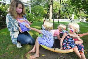 Arwen Evans prepares to read The Safe Return, a children's book she co-authored with her sister Ashley Wheelock to her children, Kit, Beatrix and Ginger at their home in Greenwich, Connecticut on Sept. 18, 2020. This is Evans second book, which is written and illustrates the normalizes mask-wearing for children during the Covid-19 pandemic.