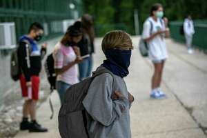 STAMFORD, CONNECTICUT - SEPTEMBER 14: Masked students wait for the doors to open after drop-off at Rippowam Middle School on September 14, 2020 in Stamford, Connecticut. Most students there are taking part in a hybrid model, where they attend in-school classes every other day and distance learn the rest. More than 20 percent of students in the Stamford Public Schools district are enrolled in the distance learning option only, due to coronavirus concerns. (Photo by John Moore/Getty Images)