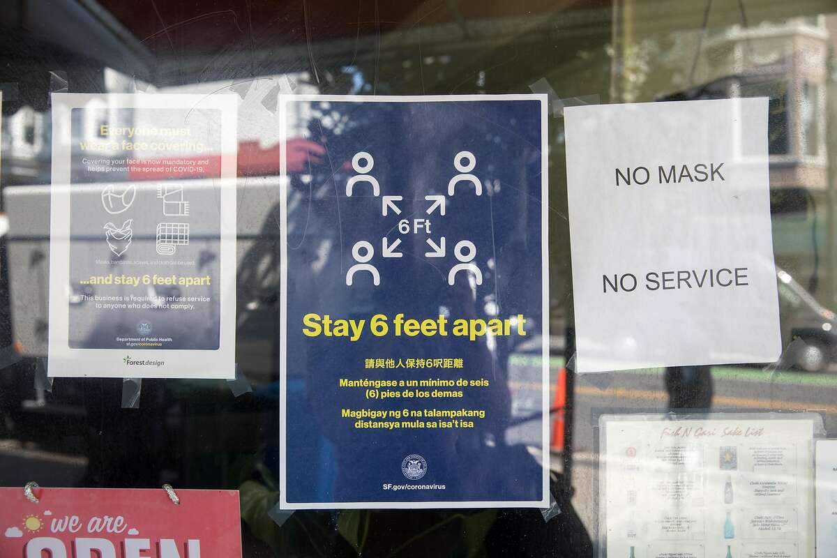 Windows in a business remind customers to wear signs and social distance in San Francisco, California on Sept. 16, 2020.