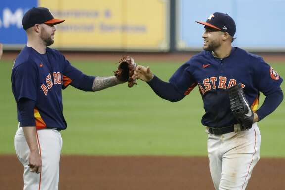 Houston Astros George Springer (4) and pitcher Ryan Pressly (55) celebrate the Astros 3-2 win over the Arizona Diamondbacks to finish the last regular season home game at Minute Maid Park, Sunday, September 20, 2020, in Houston.