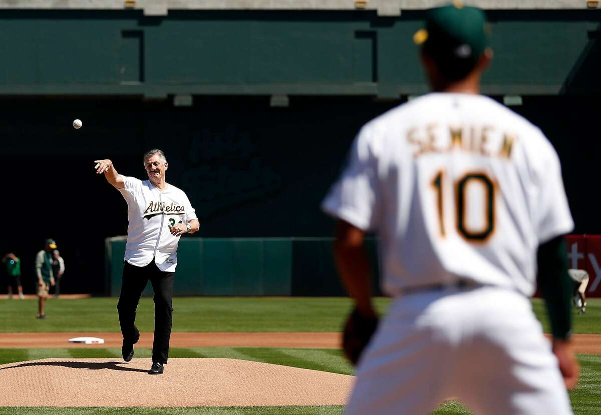 Oakland Athletics' Hall of Famer Rollie Fingers throws out ceremonial first pitch to Marcus Semien before A's home opener against Los Angeles Angels at Oakland Coliseum in Oakland, Calif., on Thursday, March 29, 2018.
