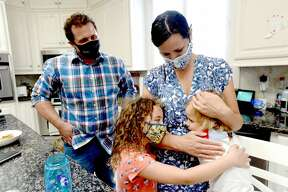 Dr. Cliff Hancock looks on as his wife Dr. Nikki Hancock gets a hug from daughters Addy (right) and Lucy, at home after a day of work caring for COVID-19 patients at Baptist Hospital. The family's normal after-work routine has shifted amid the virus and her work as a frontline healthcare provider to some of Southeast Texas' sickest patients. Dr. Hancock no lonnger walks through the door to hug annd kiss her children. She has a decontamination room set up in her garage, where after pulling in, she disrobes, putting her clothinng from the day in a bucket to be washed at week's end, scrubbs with sanitizer, then showers. After, she joinns her husband, Dr. Cliff Hancock and their three children and shifts from coronavirus caregiver to wife and mother. Photo taken Tuesday, August 18, 2020 Kim Brent/The Enterprise