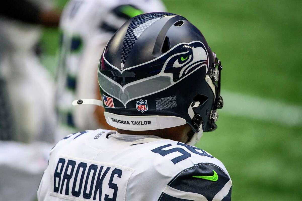 Seattle Seahawks linebacker Jordyn Brooks (56) pays tribute to Breonna Taylor during the first half of an NFL football game against the Atlanta Falcons, Sunday, Sept. 13, 2020, in Atlanta. The Seattle Seahawks won 38-25. (AP Photo/Danny Karnik)
