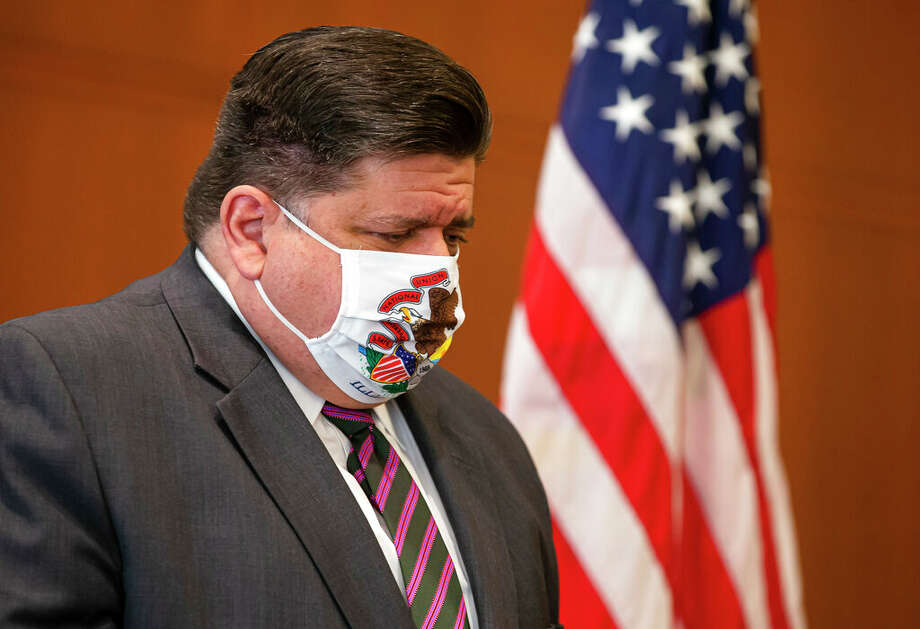 Gov. J.B. Pritzker lowers his head as Illinois Department of Public Health Director Ngozi Ezike announces seven additional deaths due to COVID-19 during a press conference about the state surpassing 5 million tests since the beginning of the pandemic. Health experts fear there could be increases in positive tests in the week ahead, as the contamination window for Labor Day opens. Photo: Justin L. Fowler | AP / 2020 The State Journal-Register