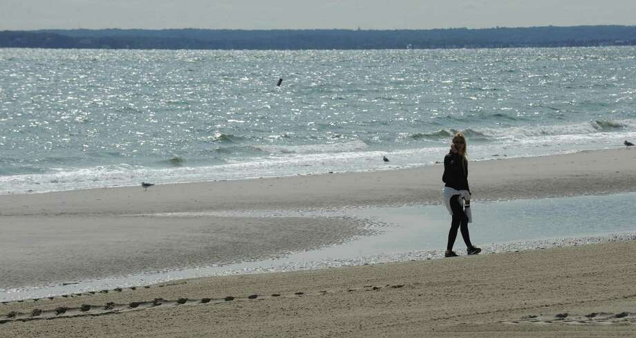 A beach visitor takes in the fresh air on the last day of summer as she takes a stroll at Tod's Point. People will need their beach cards for a month longer as they will still be required for access through Nov. 30. Photo: Matthew Brown / Hearst Connecticut Media / Stamford Advocate