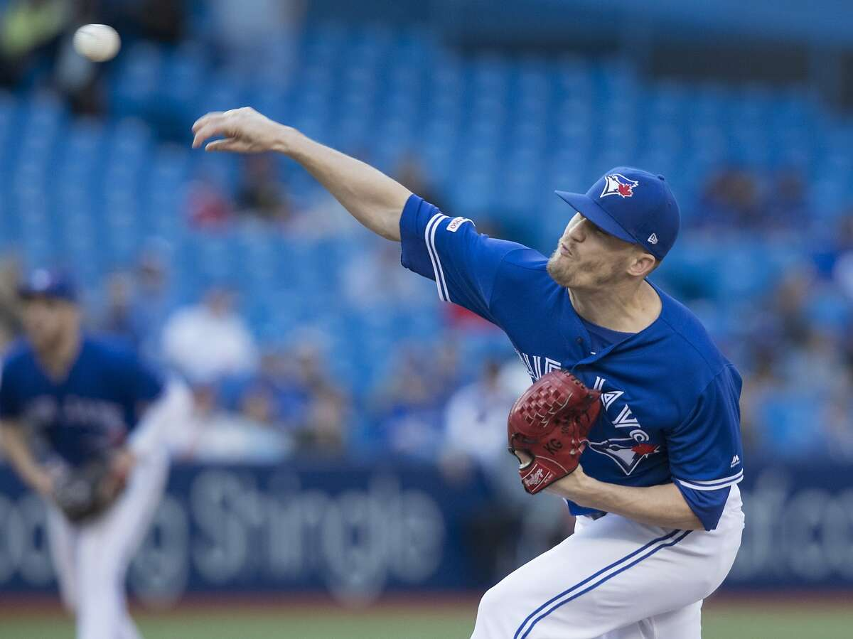FILE - In this Aug. 31, 2019, file photo, Toronto Blue Jays pitcher Ken Giles throws against the Houston Astros during the ninth inning of a baseball game in Toronto. Giles will have Tommy John surgery on his right elbow, likely causing him to miss all of 2021 and impacting the deal he will receive as a free agent this offseason. (Fred Thornhill/The Canadian Press via AP, File)