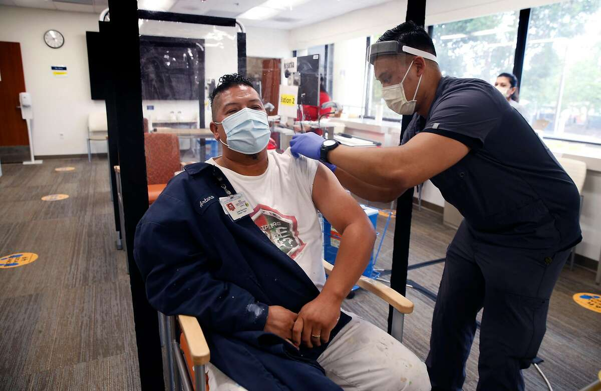 Damiel Amores (right) vaccinates Juan Sanchez against the flu at a walk-in clinic at the Kaiser Permanente medical center in Redwood City, Calif. on Thursday, Sept. 17, 2020.
