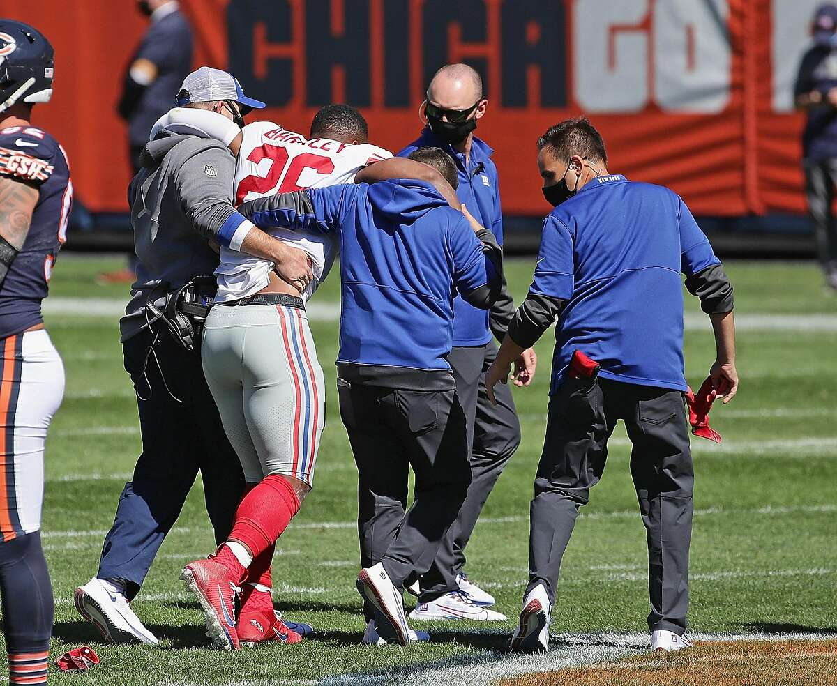 Saquon Barkley (26) of the New York Giants is helped off the field with an injury against the Chicago Bears on Sunday, September 20, 2020 at Soldier Field in Chicago, Illinois. Saquon Barkley tore the ACL in his right kneE and is out for the season. (Jonathan Daniel/Getty Images/TNS)