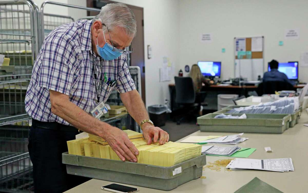 Stephen Heinrich goes through voting applications as the Bexar County Elections Department holds a briefing Monday on preparations for the Nov. 3 election.