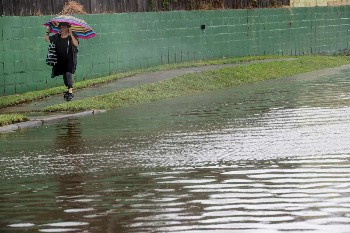 A woman walks along the edge of a street flooded by Tropical Storm Beta Monday, Sept. 21, 2020 in Galveston.
