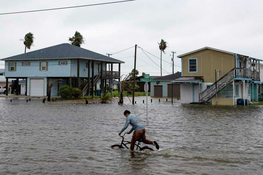 A boy rides his bike down South Magnolia Street in Rockport, Texas, as Tropical Storm Beta approaches on Monday, Sept. 21, 2020. (Courtney Sacco/Corpus Christi Caller-Times via AP) Photo: Courtney Sacco, MBR / Associated Press / Courtney Sacco