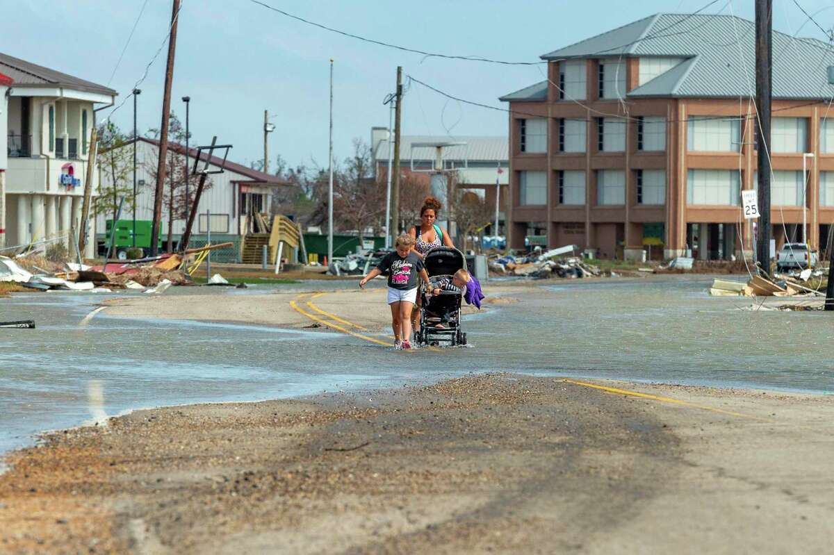 Gabrielle Jinks with her children Cheyann, JJ, and Evelyn walking along Hwy 27 in Cameron, La., as Tropical Storm Beta moves closer to shore, Monday, Sept. 21, 2020. (Scott Clause/The Daily Advertiser via AP)