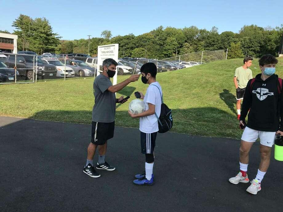 Trumbull coach Sil Vitiello checks a player's temperature prior to Monday's practice on Sept. 21, 2020. Photo: Bill Bloxsom / Hearst Connecticut Media