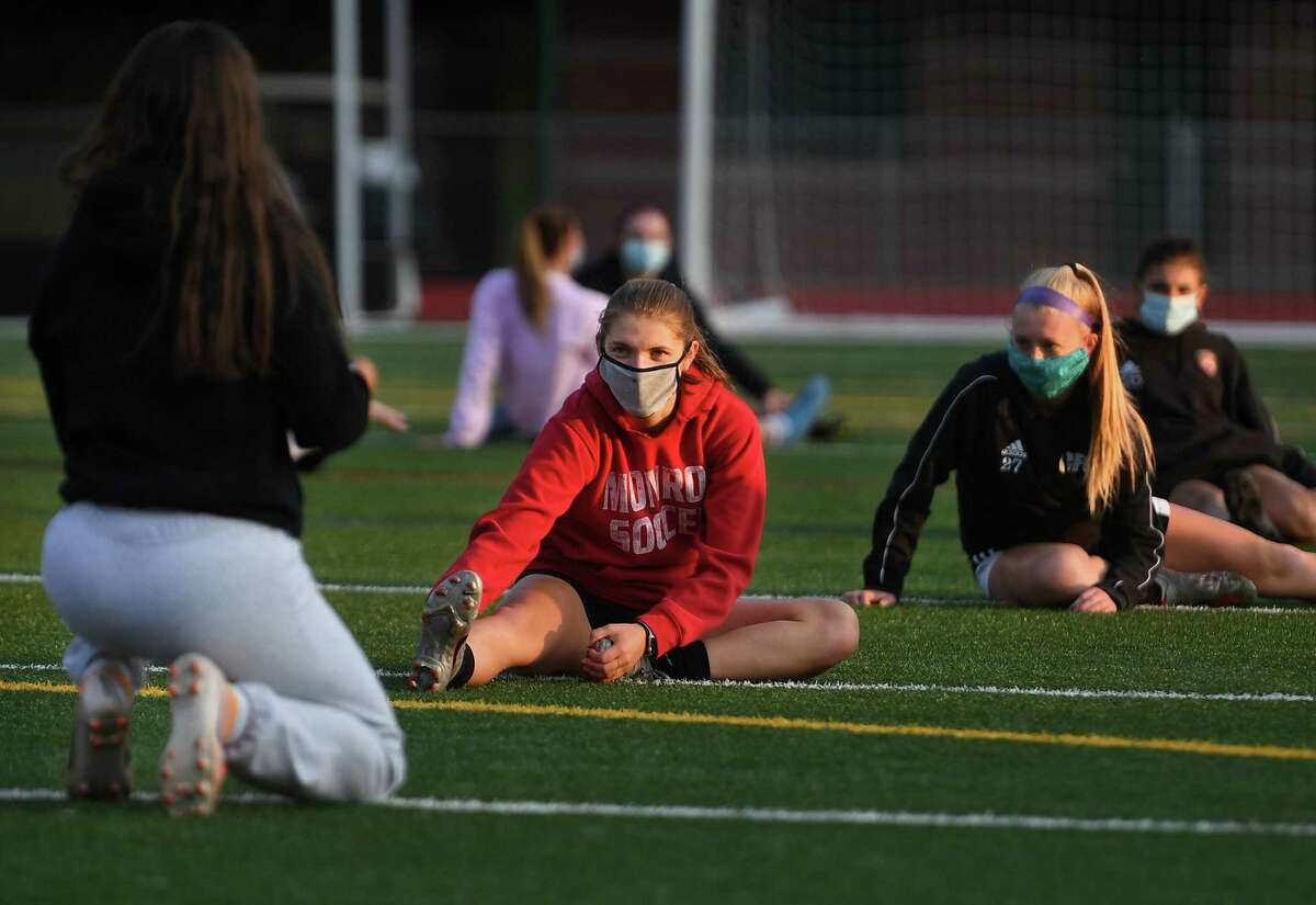 Girls varsity soccer players wear masks as they stretch before their first full team practice of the season at Masuk High School in Monroe, Conn. on Monday, September 21, 2020.