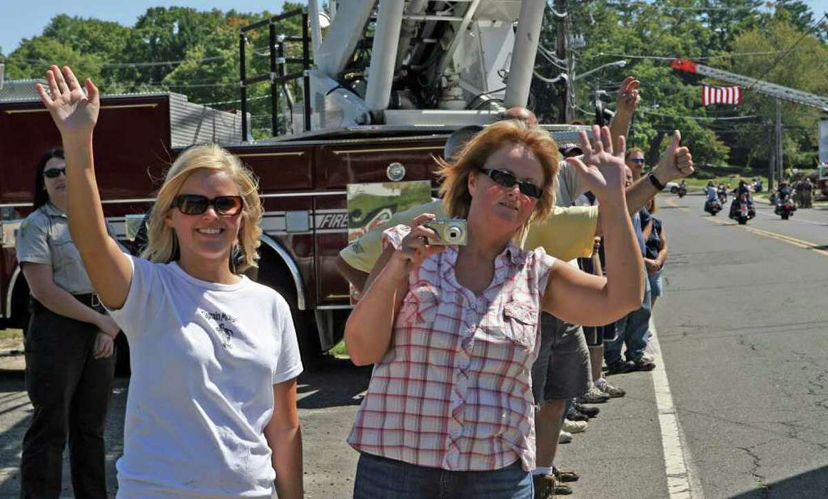 Samantha Ignahowki, left, and Alison Ignahowki, of Monroe, watch the annual CT United Ride drive down Main St. in Trumbull on August 29, 2010.