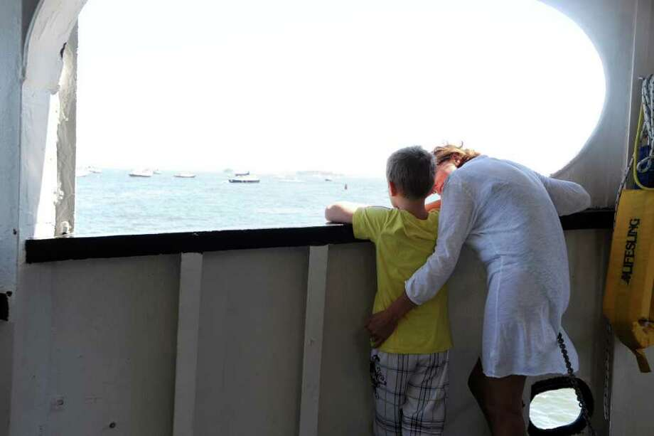 Caroline Grove, of Greenwich, comforts her son, Daniel, 8, who will be going back to Mianus School this year, while they ride the ferry to Island Beach, on Sunday, Aug. 29, 2010. Photo: Helen Neafsey / Greenwich Time