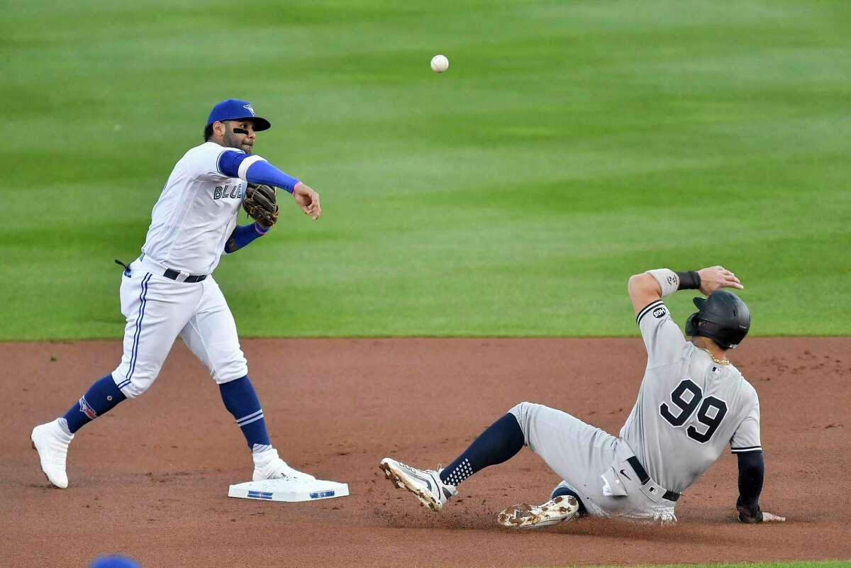 Toronto Blue Jays second baseman Jonathan Villar, left, forces out New York Yankees' Aaron Judge, right, at second and throws to first to complete a double play on Giancarlo Stanton during the first inning of a baseball game in Buffalo, N.Y., Monday, Sept. 21, 2020. (AP Photo/Adrian Kraus)