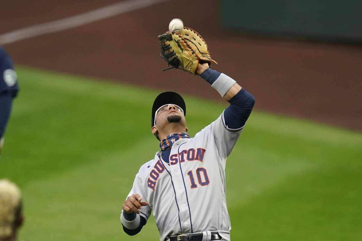 Houston Astros first baseman Yuli Gurriel catches a foul ball from Seattle Mariners' Dylan Moore for an out in the first inning of a baseball game Monday, Sept. 21, 2020, in Seattle. (AP Photo/Elaine Thompson)