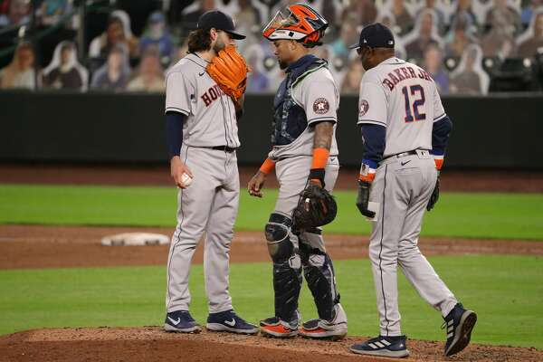 SEATTLE, WASHINGTON - SEPTEMBER 21: Lance McCullers Jr. (L) #43 speaks with Martin Maldonado #15 and manager Dusty Baker Jr. #12 after giving up a three-run home run to Evan White #12 of the Seattle Mariners in the seventh inning at T-Mobile Park on September 21, 2020 in Seattle, Washington. The Mariners lead 4-0 on the play. (Photo by Abbie Parr/Getty Images)
