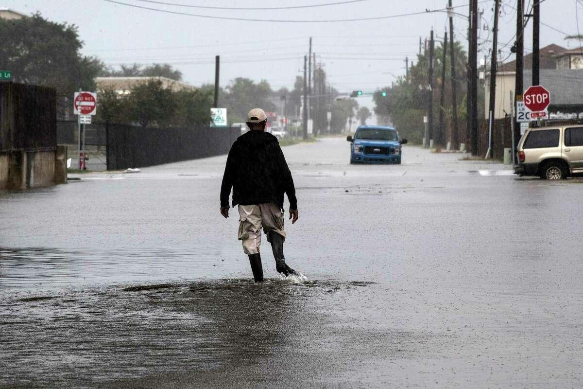 Un hombre camina a través de una calle inundada por la Tormenta Tropical Beta el lunes 21 de septiembre de 2020 en Galveston, Texas.