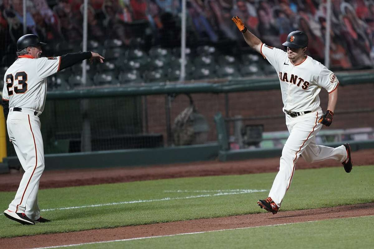 San Francisco Giants third base coach Ron Wotus, left, virtually high-fives Alex Dickerson, who runs the bases after hitting a solo home run against the Colorado Rockies during the seventh inning of a baseball game on Monday, Sept. 21, 2020, in San Francisco. (AP Photo/Tony Avelar)
