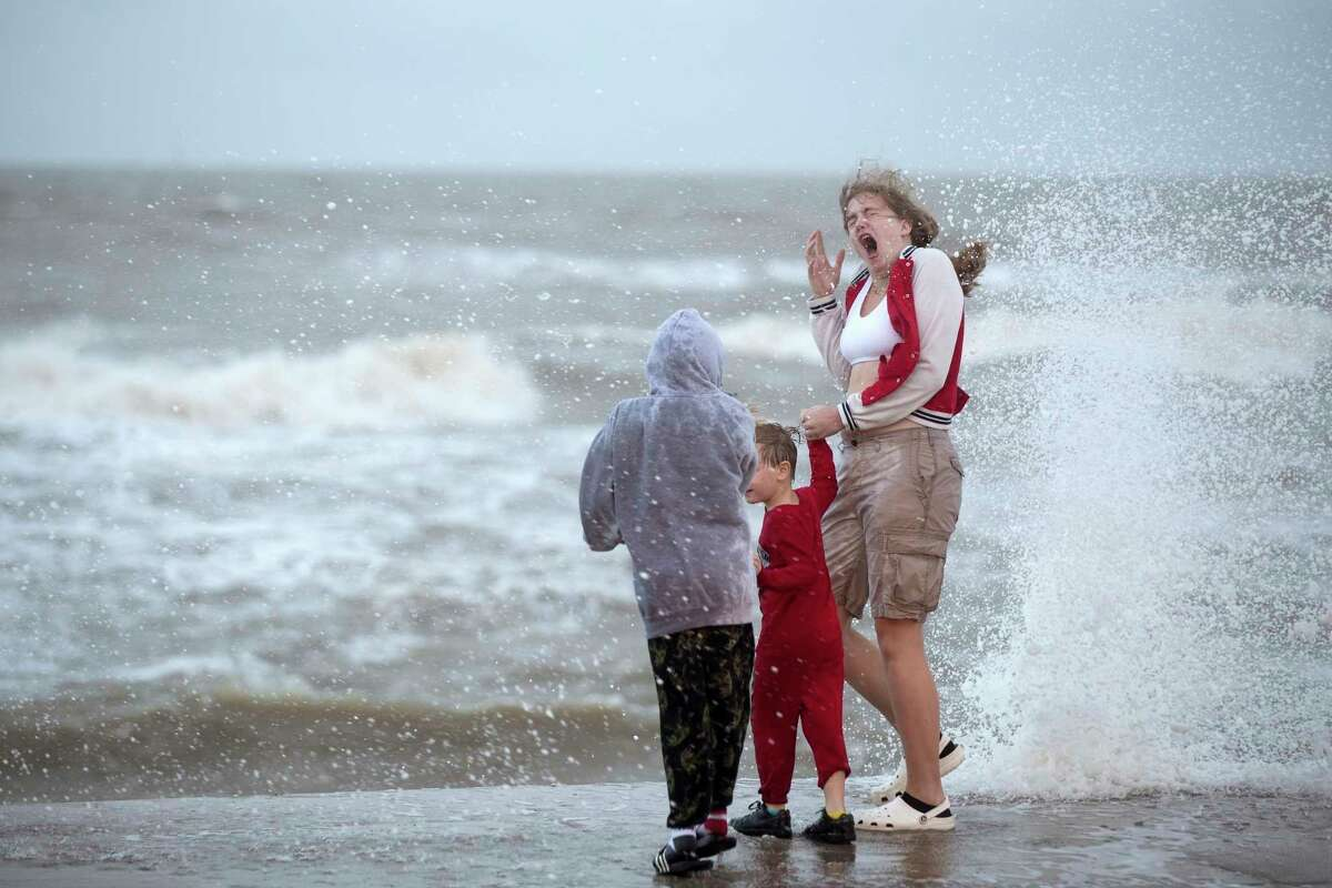 Reighny Knight, reacts as she, Elijah Melendez, left, and Peyton Knight, are splashed by waves churned up by Tropical Storm Beta as it moves toward landfall Monday, Sept. 21, 2020, in Galveston, Texas. (Brett Coomer/Houston Chronicle via AP)