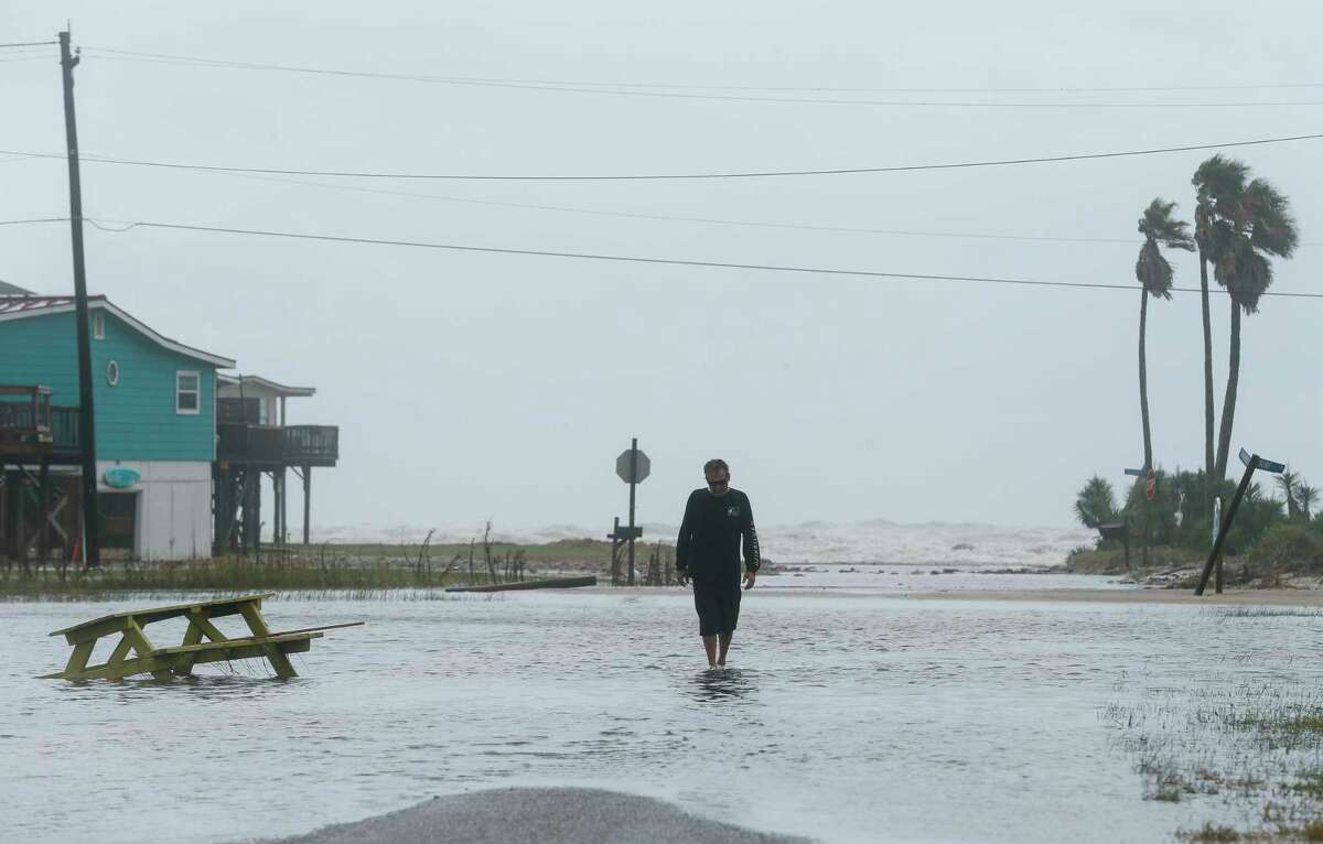 Mark Wilson walks on Thunder Road, which was flooded during a tidal surge, before Tropical Storm Beta makes landfall Monday, Sept. 21, 2020, in Surfside, Texas. (Godofredo A. Vásquez/Houston Chronicle via AP)