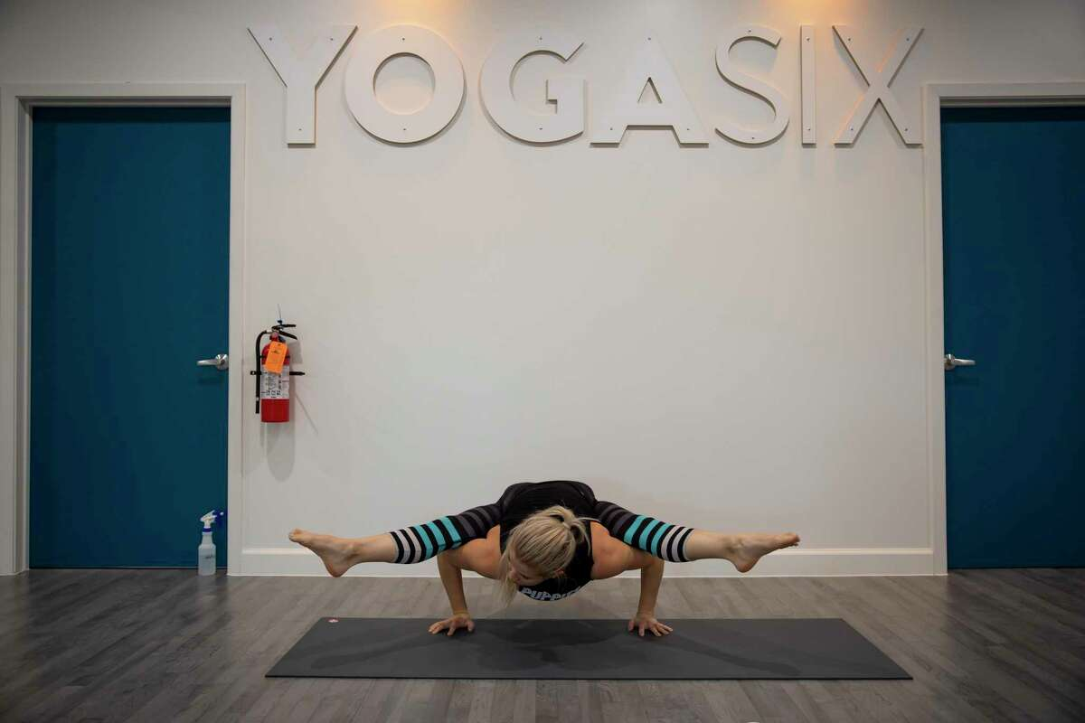 Lauren Walker demonstrates yoga techniques she uses when leading classes at YogaSix in The Woodlands, Thursday, Sept. 17, 2020. YosaSix installed a hi-tech German air filter system to help with fight against the spread of COVID-19.